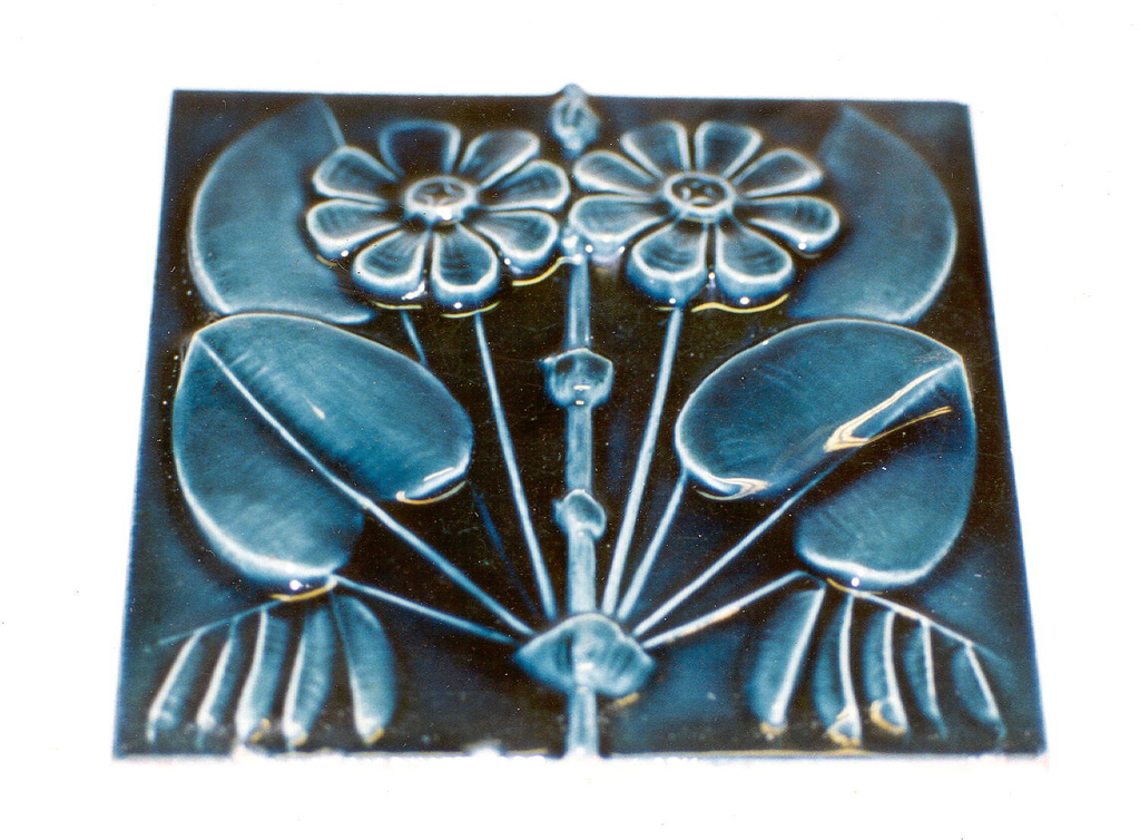 """Square, molded tile with inscription impressed on reverse set in a double line frame: """"J. & J.G. Low, Patent, Art Tile Works, Chelsea, Mass. U.S.A. Copyright 1881 by J & JG Low"""". Face of tile decorated with pair of stylized daisies which grow from a bamboo stem. Leaves are heart shaped. Tile is glazed teal-blue."""