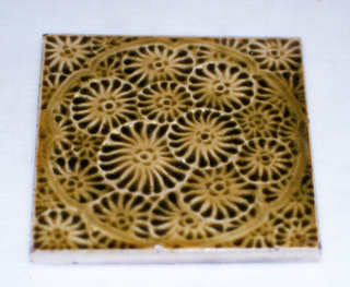 Square, molded tile of white clay, reverse has impressed set of double-line frame. Face is decorated with all-over daisy flowers under superimposed circular frame of narrow brackets; glaze pale brown crackle.