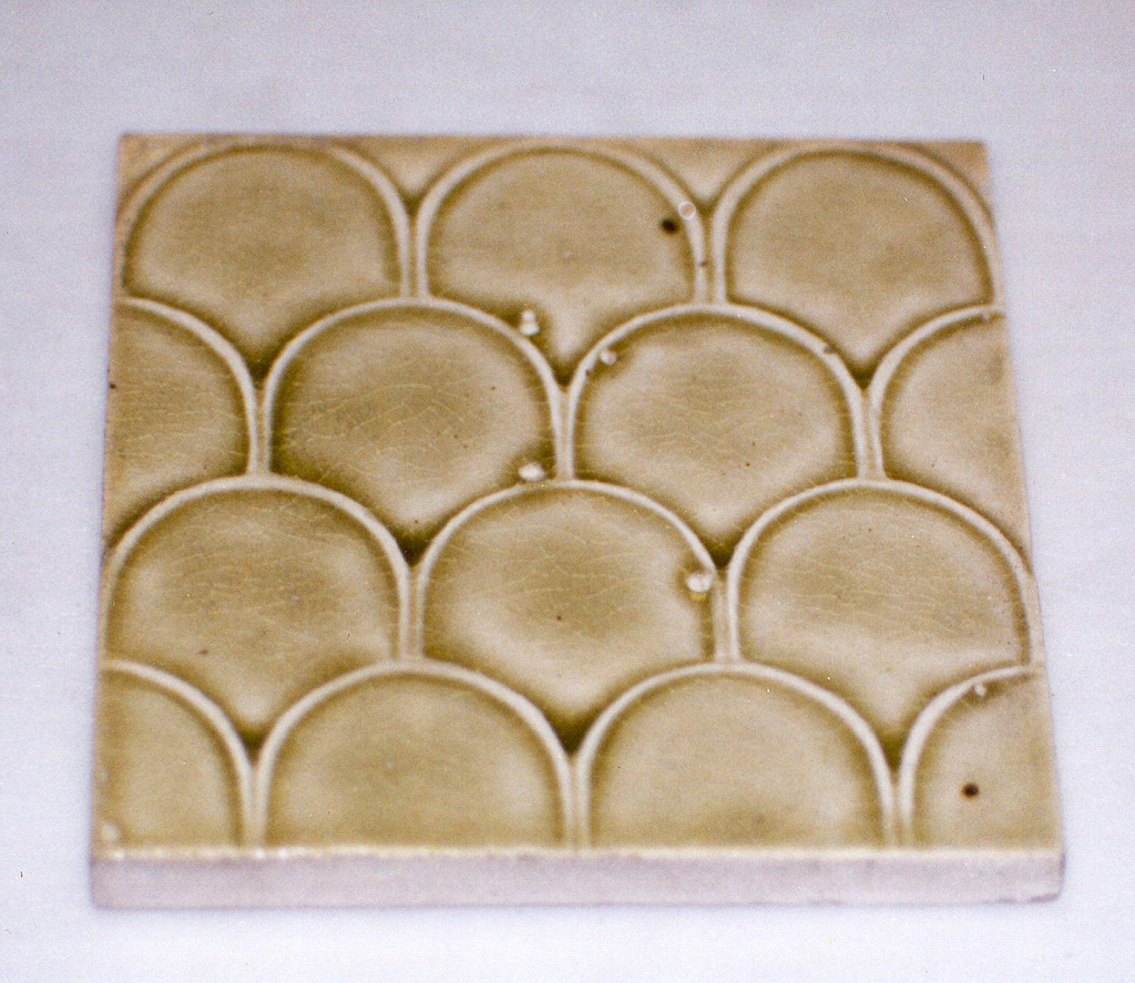 """Square molded tile of white clay, impressed on the back with inscription: """"J. & J.G. Low, Patent art Tile Works, Chelsea Mass. U.S.A., copyright 1881 by J. & J.G. Low"""". Face of tile is stamped with imbricated scale pattern, glazed with a green crackle glaze."""