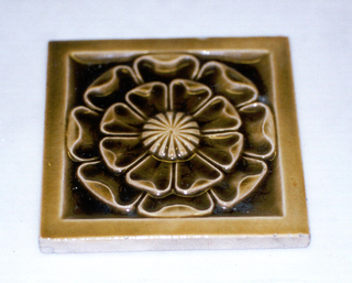 """Square molded tile made of white clay, impressed and inscription: """"J. & J.G. Low, Patent Art Tile Works, Chelsea Mass. U.S.A., copyright 1881 by J. & J.G. Low"""". Tile face is decorated with a stylized flower having two rows of concentric pedals, center rosette, framed in plain border; glazed dark teal blue."""