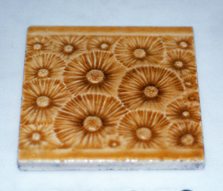 Square molded tile made of white clay, Tile face is decorated with stylized dandelions (gone to seed) in an all-over pattern set between plain horizontal borders. Tile is painted deep honey-brown crackle glaze.