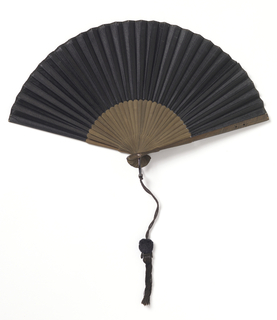 Pleated fan. Black organdy. Bamboo sticks with dark stain. Rivet set with stone. Cotton tassel.