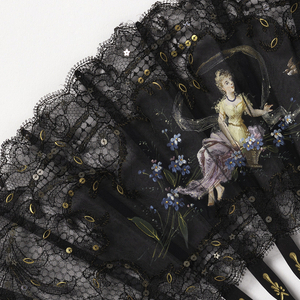 Black lace fan with two appliquéd black silk cartouches, hand painted with scenes: one of a reclining woman with a basket of flowers, the other a putto with a tambourine. Embroidered with gold and silver spangles. Sticks are ebony with gilt decoration and piqué with steel discs.