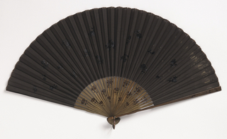 Pleated mourning fan. Black silk leaf embroidered with black silk flower sprays in satin stitch. Bamboo sticks stained and painted with small graduating flowers in black oil. Metal bail.