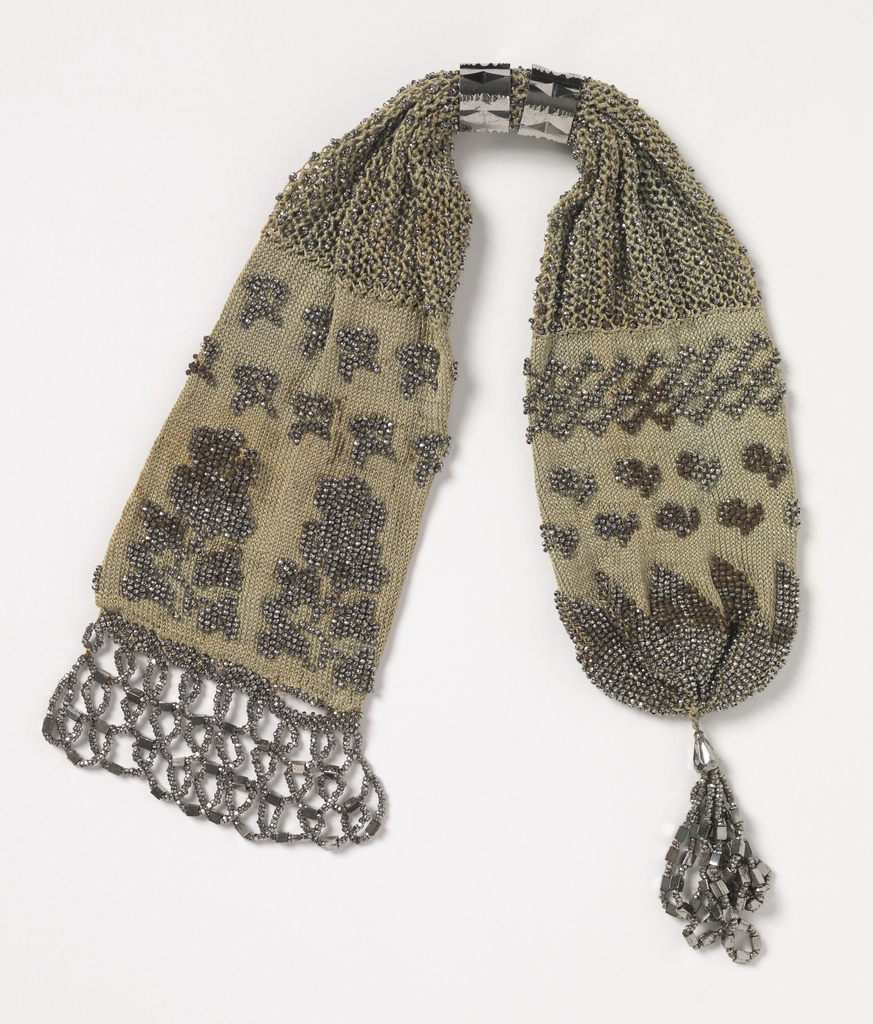 Miser's purse knitted in gray silk with steel beads, with two steel rings. Finished at one end with looped fringe of steel beads, and at the other with a tassel of steel beads.