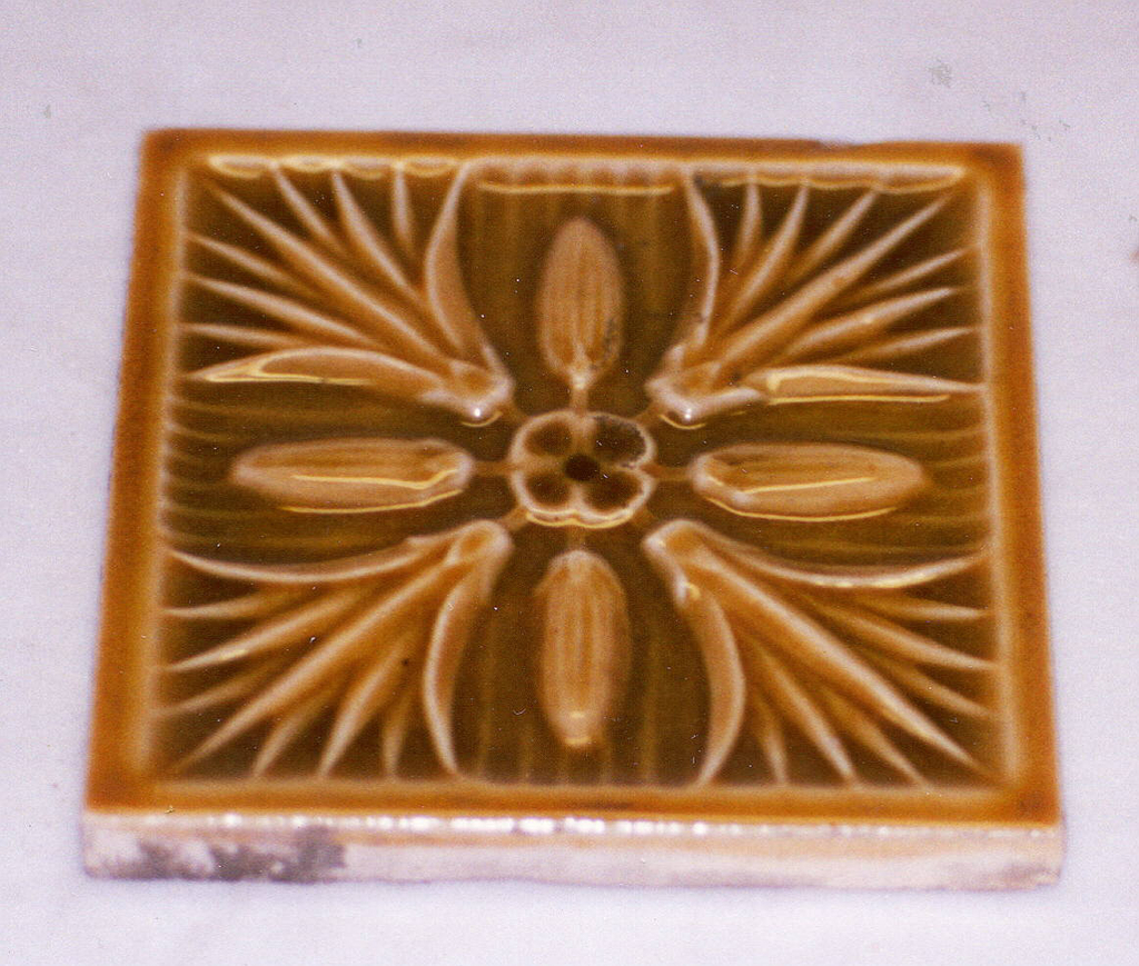 """Molded, square tile of white clay, reverse has imprinted inscribed: J & J.G. Low Patent Art Tile Works/ Chelsea, Mass. U.S.A./ copyright 1881 J & JG Low"""". - set within a double line frame. Tile face ornamented with eight piece figure made up of central rosetted and radiating lotus blossoms and buds, plain frame outside of the tile; mustard brown, crackle glaze."""