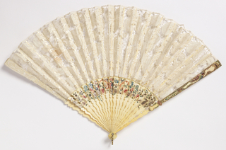 Pleated fan. Leaf of 17th century white Milanese bobbin lace. Carved and painted ivory sticks with flowers and feathers. Guards carved with baroque detail and painted. Rivet is set with faceted glass. Gilt metal bail.