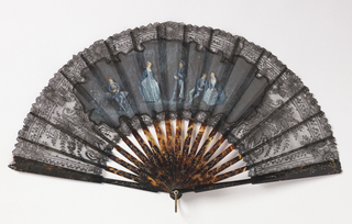 Pleated fan. Black machine-made lace leaf with appliquéd gauze painted with blue gouache showing two couples and a musician. Gilded tortoise shell sticks with inlaid steel piqués. Gilt metal bail.