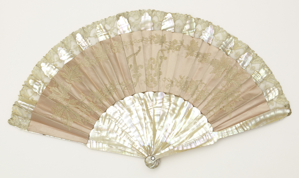"""Pleated fan, pink satin leaf with applied decoration of white lace. In the center is the monogram: """"F.S."""" Sticks are plain mother-of-pearl."""