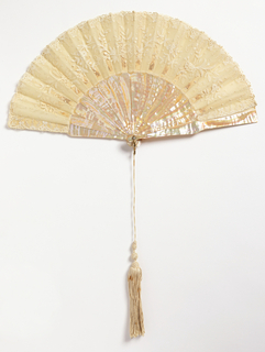White fan leaf. OBverse: lace with floral design. Reverse: plain gauze. Mother-of-pearl sticks. Brilliant set in metal pin. White silk tassel with decorative knots.