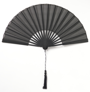 Pleated fan. Black organdy leaf. Carved black wood sticks incised with scrolls and flowers. Black tassel.