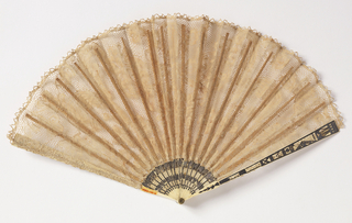 Pleated fan. Bobbin lace leaf in natural linen color. Pierced ivory sticks piquéd, incised and silvered.