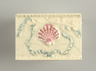 "Rectangular molded tile of white clay; reverse has row of nine alternating depressed and raised bars with inscription: ""C E Tile Co Anderson, Ind. USA"". Face of tile decorated with scallop shell suspended from beaded swag, framed in ribbons at top, crossed branches bottom. Horizontal tile edges in relief. Underglaze pink, blue. Overglaze gold."