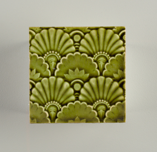 Square, molded tile of white clay, reverse side imprinted with seres of parallel bars and stamped: 126,23. Face decorated with all over pattern of fan shaped figures; leaf green glaze.