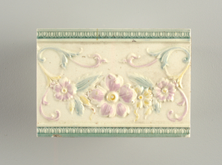 "Rectangular molded tile of white clay; reverse has nine horizontal bars alternately depressed and embossed and inscription: ""Cambridge"" with catalogue number 471. Tile face shows scrolling flowers and vines framed between horizontal egg-and-dart moldings top and bottom. Underglazed pink, yellow, green."