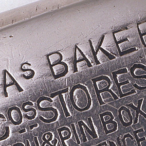 """Rectangular, curved corners and sides, the front inscribed """"CHAs BAKER & Cos Stores, Match & Pin Box, Price Two Pence, 271 to 274 High Holborn, 41 & 43 Ludgate Hill, 137 to 140 Tottenham Court Rd St.  [T.Turner's manufacturer's trademark stamped on lower left; Rd. 26844 on lower right.] Reverse inscribed """"Gentlemens & Boys Superior Clothing, Hosiery, Shirts, Hats, Boots & C. 25 Per Cent Under Usual London Prices to Keep Pace with the Civil Service Stores."""" Interior match container revealed when inscribed exterior sheath is pulled open at side; both exterior and interior pivot on attached pin at bottom center. Striker recessed on side."""