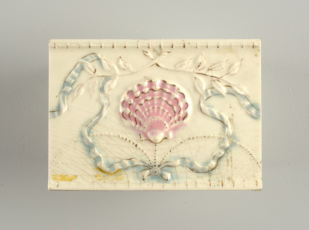 """Rectangular molded tile of white clay; reverse has row of nine alternating depressed and raised bars with inscription: """"C E Tile Co Anderson, Ind. USA"""". Face of tile decorated with scallop shell suspended from beaded swag, framed in ribbons at top, crossed branches bottom. Horizontal tile edges in relief. Underglaze pink, blue. Overglaze gold."""
