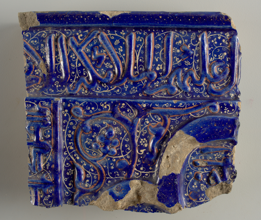 Square fragment. Blue, with three planes of raised ornament consisting of Kufic and Neskhi characters and a scrolled stem with fruit, outlined with light reddish brown. Painted over-all pattern of delicate scrolls in pinkish white.