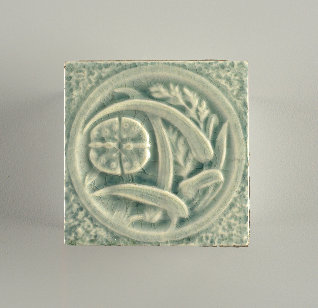 Tile in light blue-gray with white, depicting a circle filled with leaves and plant forms in relief.