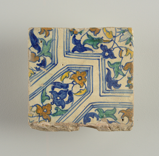 Portion of a design composed of geometrical shapes enclosing conventionalized flowers and foliage; painted in blue, green, yellow and brown.
