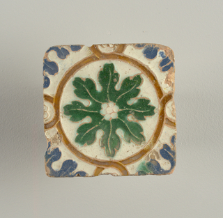 Moulded in low relief, with white, blue, green and light brown glazes. Interlacing bands forming tangent circles, large and small, enclosing green and blue foliage forms.