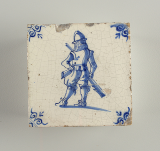 Square tile, blue on white. Soldier with helmet and breastplate standing with back in three-quarters view. Left arm akimbo, right hand at side, holding gun. Symmetrical scroll ornaments in the corner.