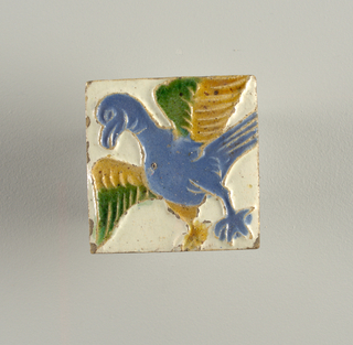 Incised with figure of an eagle, placed diagonally; raised ridges enclosing areas of blue, green and yellow coloring, against a white field.