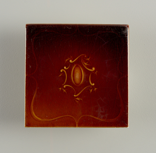 """Square, molded tile of white clay; reverse has series of eleven horizontal bands alternately raised and depressed with inscription: """"U.S.E.T.W."""". Tile face decorated with upright oval medallion framed in leaves and arabesques; yellow-brown crackle glaze."""