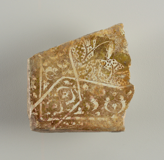 Four-sided, the lower left corner a right angle. White ground with iridescent olive green decoration consisting of a fragmentary horse and rider and a strapwork border containing conventionalized plant forms.