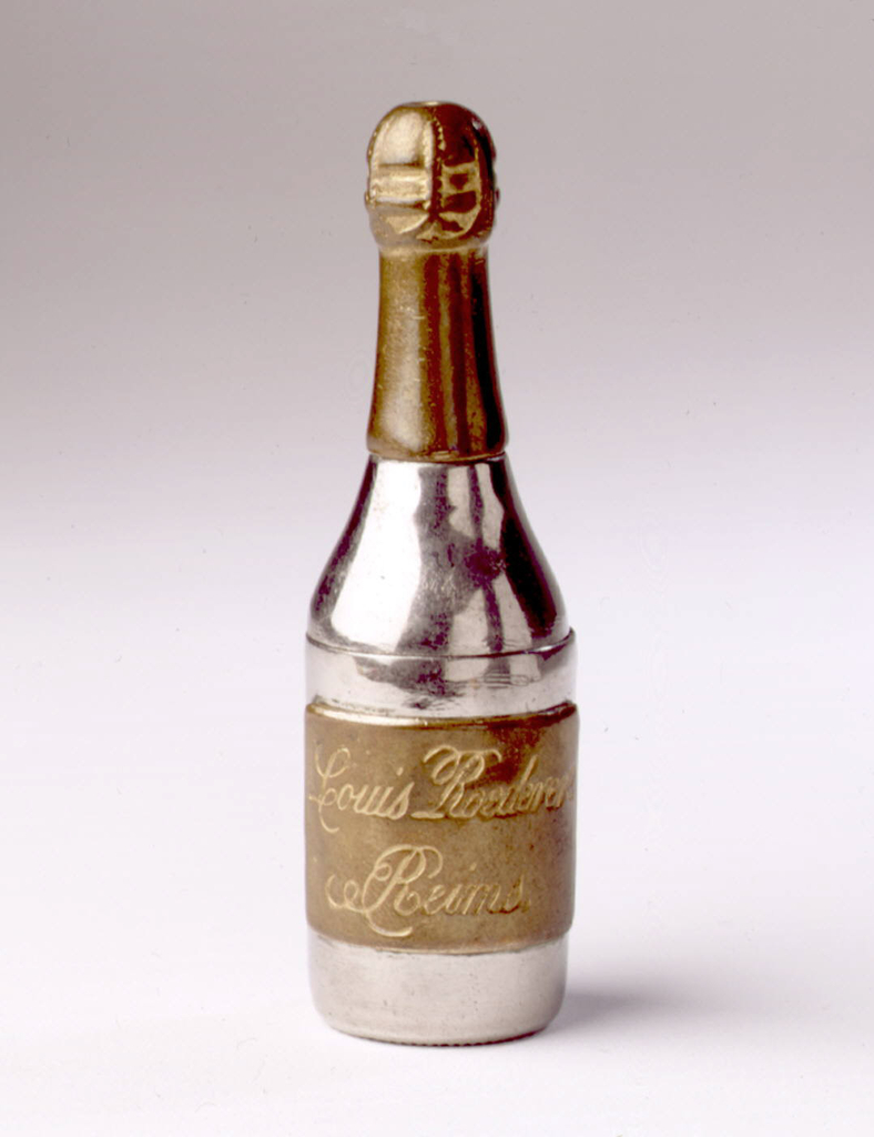 "In the form of a champagne bottle, the body silver color, the wrapped cork and neck brass , the label brass: inscribed ""Louis Roederere, Reims"". Base of bottle neck (lid) hinged at back. Striker on bottle bottom."