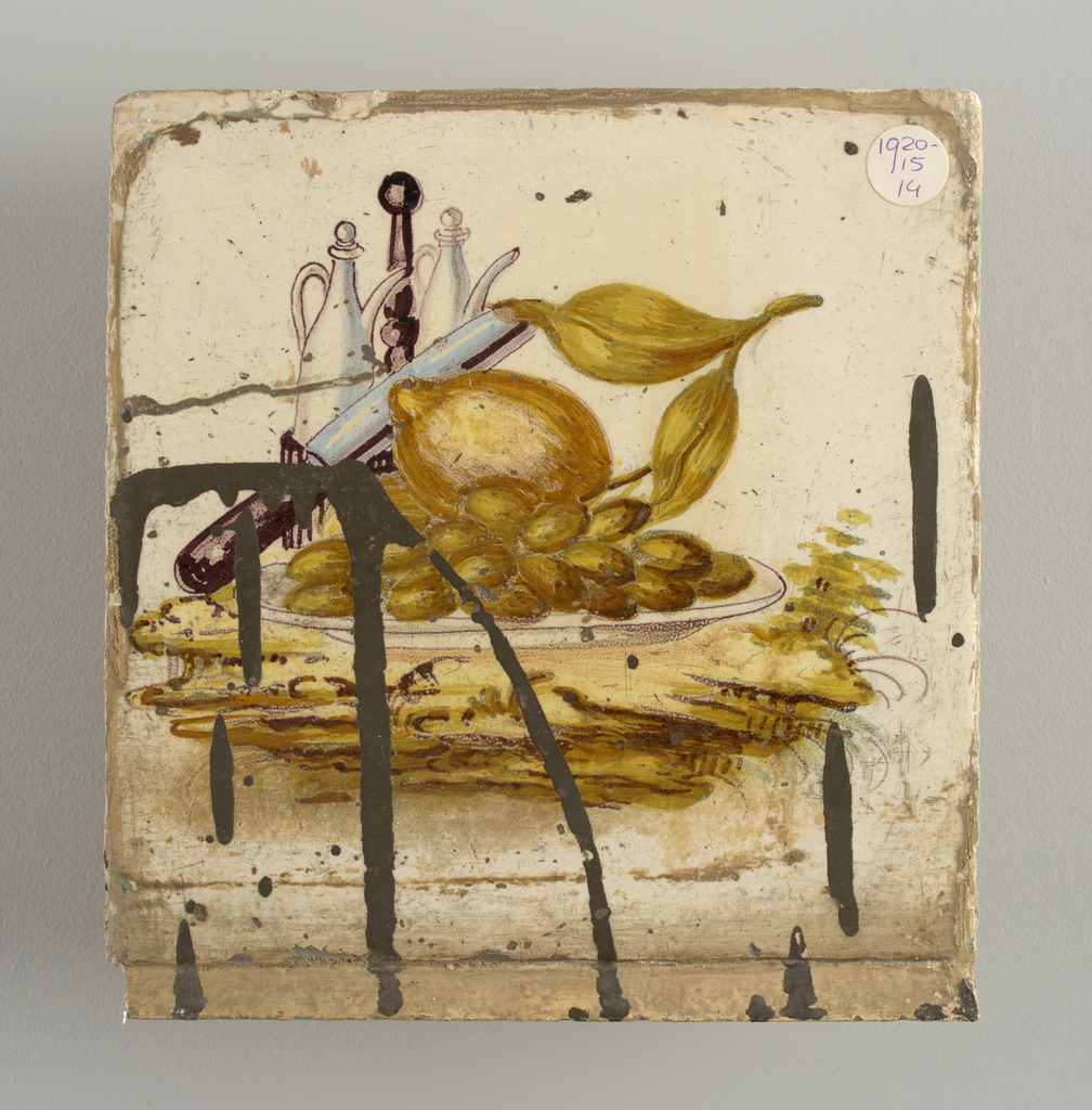 Still life of lemon and grapes on a plate, a knife, and oil and vinegar flasks.