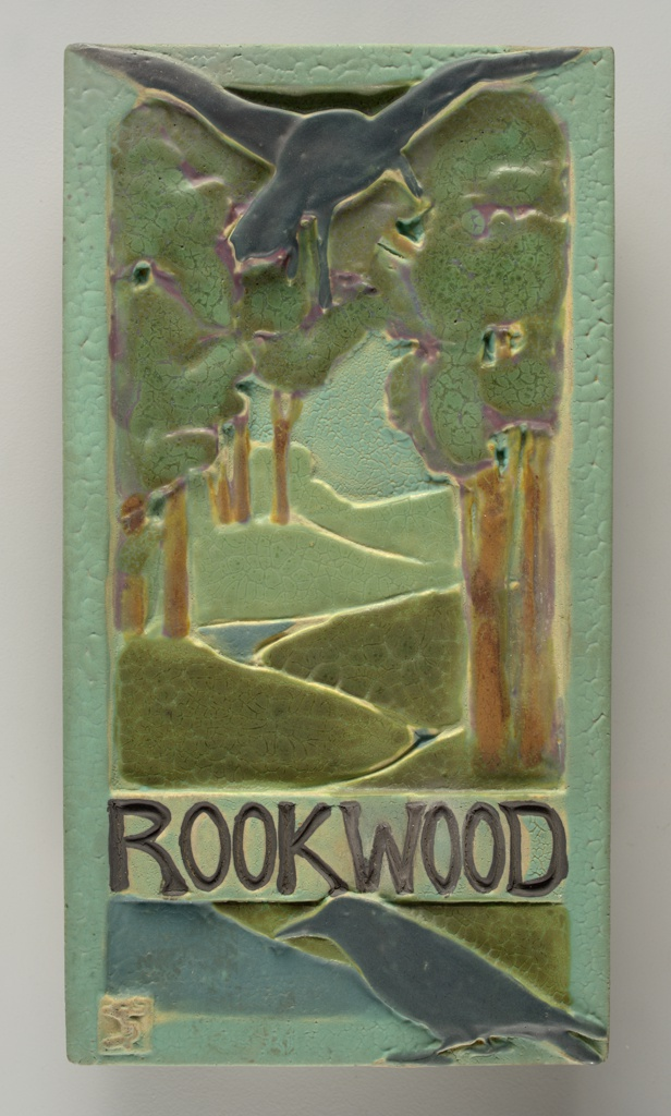 "Tile ""Rookwood"" advertising sign with rocks, forest scene. Rookwood Faience.   Rectangular plaque made of coarse white clay, molded. Design in relief of landscape with trees and winding river, with two ravens or rooks. One bird with outstretched  wings at center top of plaque, the other perched at bottom, below Rookwood logo. In various colored mat glazes, some with cracklature: dark and light greens, brown, tan, pale sea-green, fushia and black. Border and sides in a pale sea-green. Back not glazed."