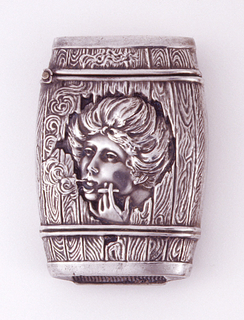 In the form of a wooden barrel, with simulated wood grain; the head of woman smoking is seen in relief through jagged edged, open reserve in center. Upper part of barrel hinged on left. Striker on bottom.