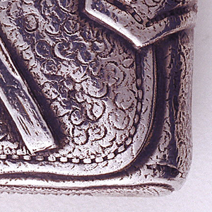 Rectangular, with curved sides featuring raised, trompe l'oeil decoration simulating a soft, textured, belted, tobacco pouch, folded over with flap at front, as well as match and one dime tucked into belt; reverse decoration simulates pinched belt loop with belt running through it; remnant of red color on match tip. Upper part of pouch or lid hinged on left side. Striker on bottom.