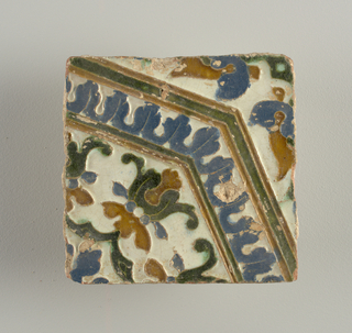 Moulded in low relief, with white, blue, green and brown glazed, forming an octagonal motif, with conventionalized floral and foliate forms.