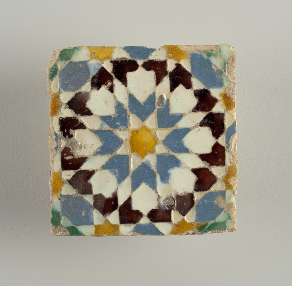 White, yellow, green, blue and brown glazes, in low relief. Gepmetrical design.