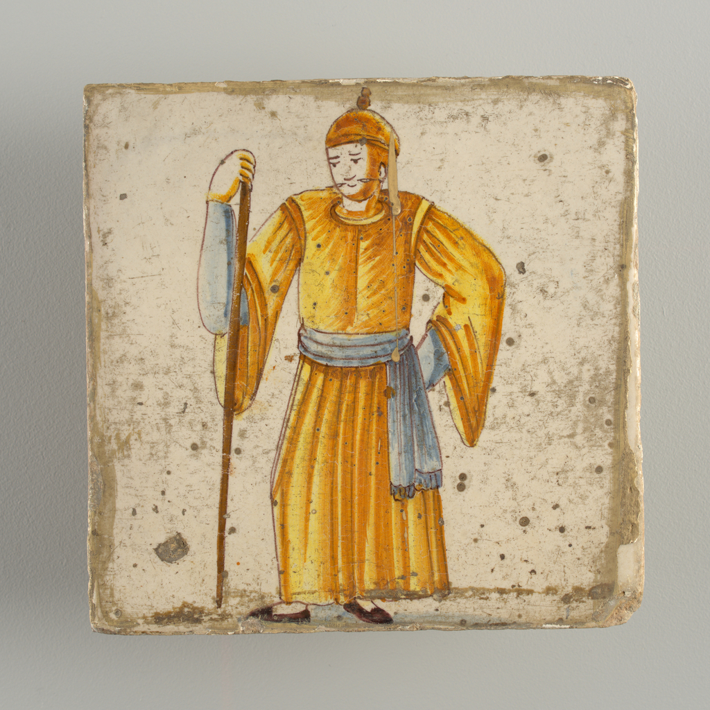 Standing man, dressed in long yellow costume and blue under sleeves and belt; leaning on long stick which he holds in his right hand. Chinoiserie type of decoration.