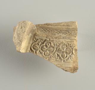 Irregular fragment with flanged edge and ornament in relief consisting of quatrefoil and chain motifs surmounting an incised wavy line. Pearly iridescence.
