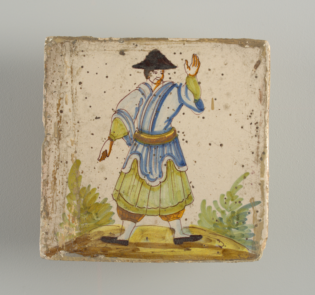Standing man, dressed in green short skirt and scalloped blue coat, wearing black coolie hat; his left hand is raised, the right points downward. Chinoiserie type of decoration.