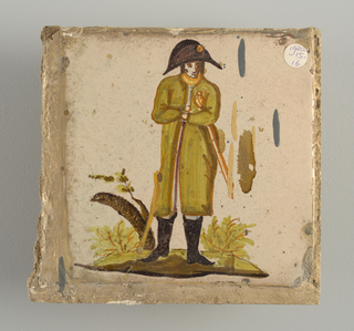 Soldier in black boots, green coat and bicorn hat, clutching a sword under his left arm. Tree trunk with a few leaves at the left.
