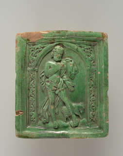 On glazed rectangular face, a relief representing S. John with the lamb within a decorated arch. The remainder of the tile, including the heavy box-like projection behind the face, is unglazed.