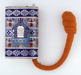 Rectangular, with rounded sides; polychrome enameled decoration of abstracted figures and geometric patterns; in the center a plain, A-framed reserve with engraved initials; a gold colored tinder cord with knot at end is housed in side compartment, attached by hook and chain that may be pulled from knob at top. Flat lid hinged on top. Striker on bottom.