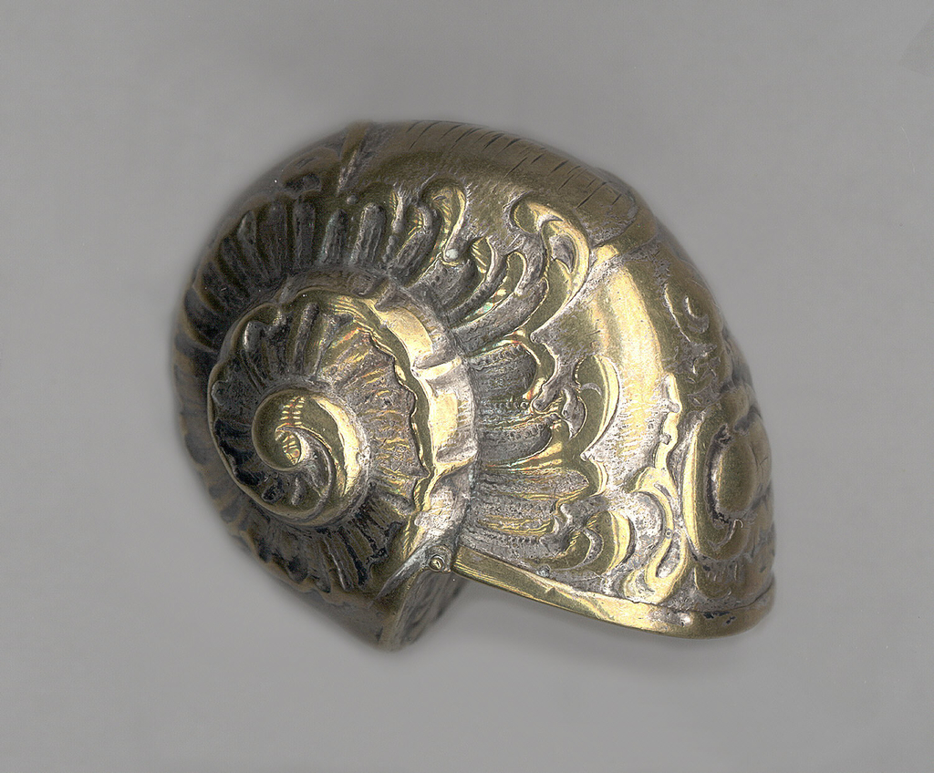 In the form of a snail shell, with raised scroll work and gadrooning on sides, decorative cartouche at top near lid, decorative shell motif on lid, which flips open at wider, flat end, hinged at center, c-scrolls below. Worn hatch marks on back possibly intended as striker.