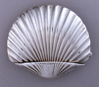 In the form of a scallop shell, ribbed surface, striker on back side.  Hinged lid, opens along top edge.