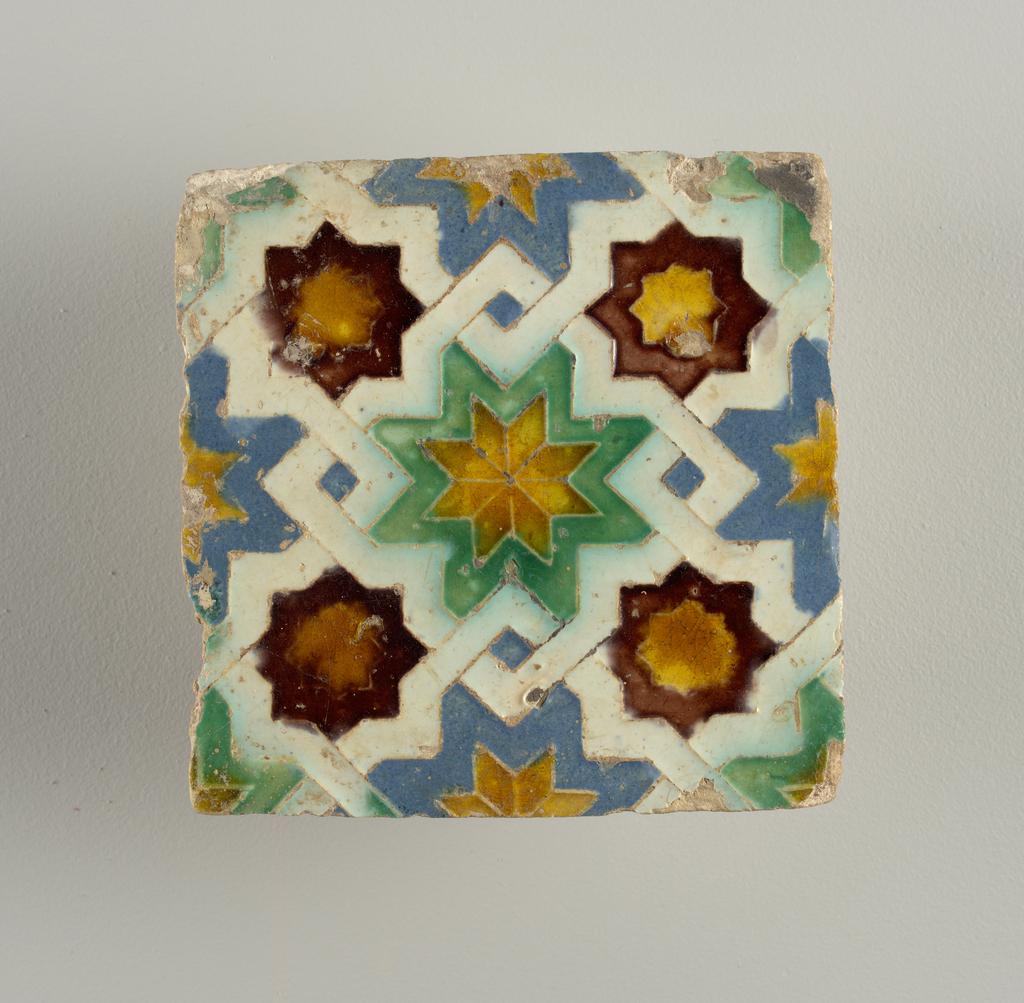Esmalte blanco, amarillo, verde, azul y marrón, en bajo relieve.  Diseño geométrico, con estrellas de ocho puntas y bandas entrelazadas.
