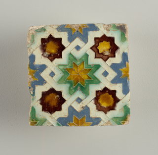 White, yellow, green, blue and brown glaze, in low relief. Geometrical design, with eight-pointed stars and interlacing bands.