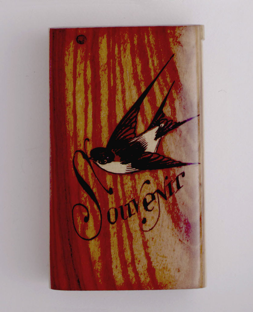 """Oblong, vertical sides curved, with image of a swallow in flight, rendered in inlaid woods and black paint, under which is the inscribed word """"Souvenir"""" in black. Inscribed in black on reverse is """"Nice."""" Simple flat lid, attached to metal pin, hinged on left side. Striker of sandpaper is recessed into bottom of box."""