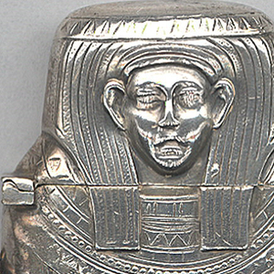 In the shape of an Egyptian sarcophagus for a king or queen with hieroglyphs running down central band on front and reverse. Link attached to side. Head serves as lid, hinged on side, thumb catch opposite at shoulder. Striker recessed in bottom.