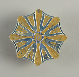 "Octagonal tile with curved sides and rounded points, decorated with starburst-like design in brown and blue. At center, ""ETC"" [?] in circle."