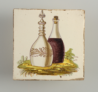 A glass carafe with purple wine and a faience bottle with fancy stopper and wreath decoration placed on some indistinct greenery.